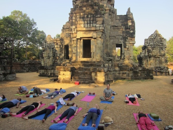 Doing yoga infront of a temple in Cambodia on an Escape to Shape holiday